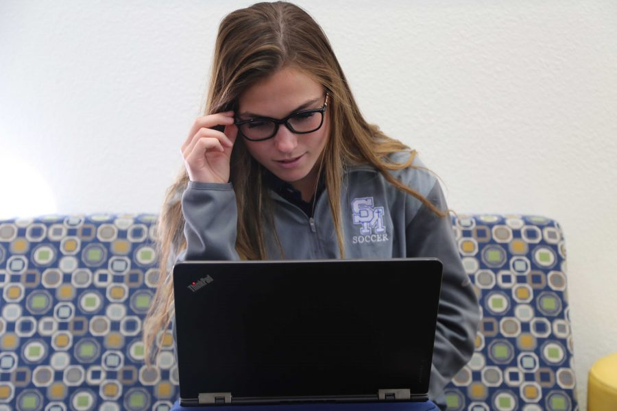 Junior+Madison+Louderback+looks+at+her+Lenova+Yoga+tablet+with+a+new+view+and+new+prescription+glasses.