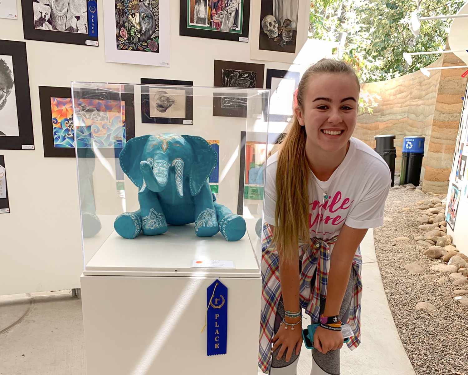 Proud of her award-winning art, Mulvihill stands next to her displayed work.