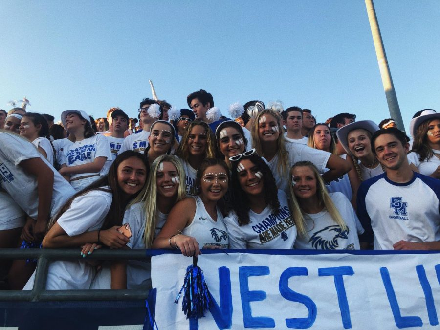 A+group+of+seniors+cheering+in+the+nest+during+a+white-out+football+game.+High+school+is+all+about+enjoying+the+little+moments.+