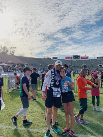Sophia VonGierke and her dad stand in Rose Bowl stadium after finishing the Pasadena half marathon. They wear their medals of victory.