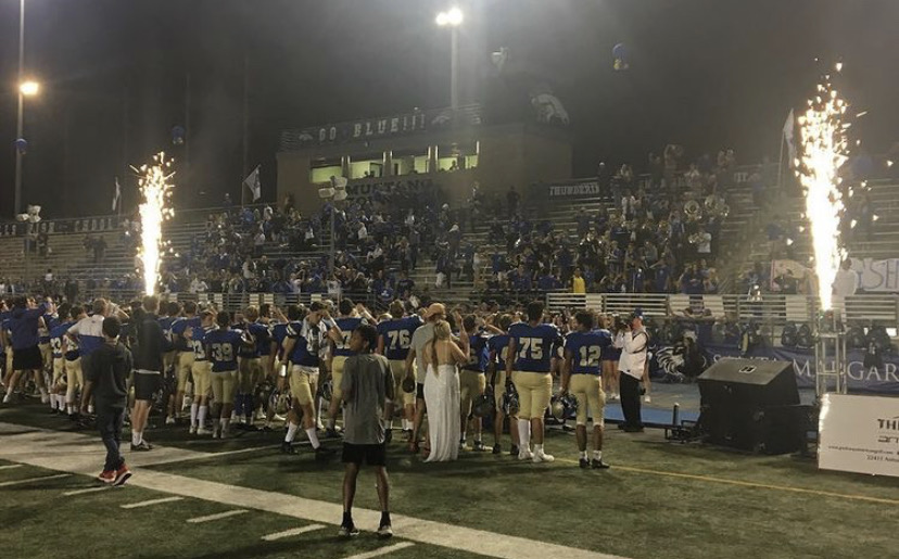 Football stands for the Alma Mater after a HOCO win.